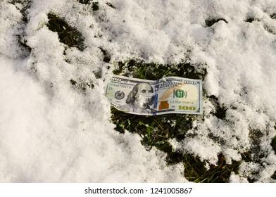 Hundred dollar US bill under snow on a lawn