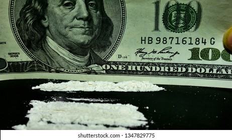 A hundred dollars bill and a lot cocaine. The separation of cocaine on the line. Preparation of drugs for use.