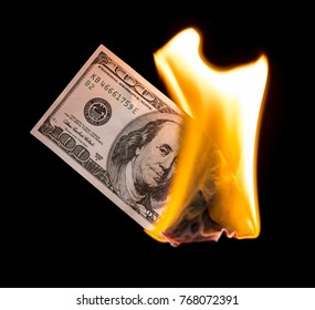 a hundred dollars burn in a fire on a black background