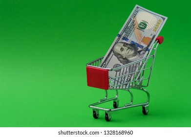 Hundred dollars note in a basket shot on chroma key. Studio shot of little tiny metal shop basket with 100 dollars note shot on green screen.