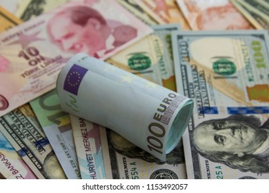 Hundred Euro banknote rolled on American Dollars and Turkish Liras.Close up taken.Exchage rate between dollar,euro and lira.