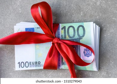 Hundred euro banknotes on a stack with red bow. Gift, bonus or reward concept