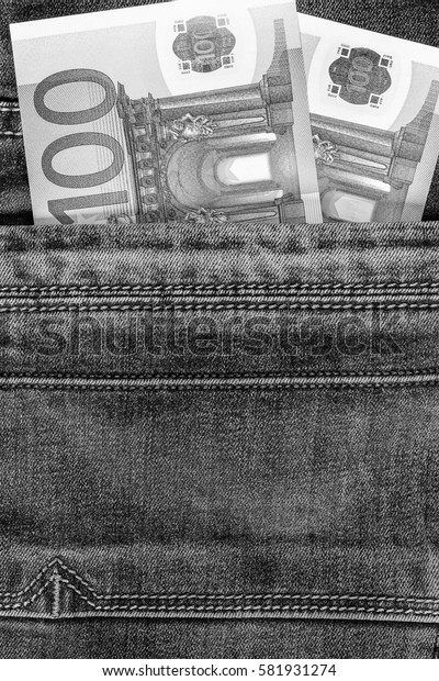 Hundred euro bill in the pocket of  blue jeans. Cash money. Black and white image.