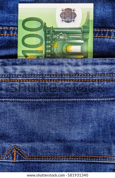 Hundred euro bill in the pocket of  blue jeans. Cash money.