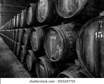 Hundreds of barrels, or pipes, of vintage port are stacked up in a long row to age in a winery in Portugal.