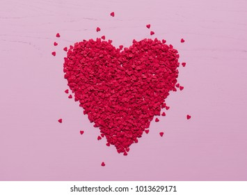Hundreds of tiny, red heart-shaped sugar sprinkles laid out as flay lay in big heart shape as symbol for romantic love on light pink wooden background for Valentine's Day