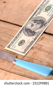 Hundreds of US dollars with knife on old wooden plank