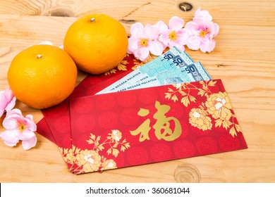 Hung Bao or red packet with Good Fortune Chinese character filled with Malaysia Ringgit currency, displayed with mandarin oranges