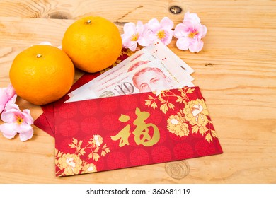 Hung Bao or red packet with Good Fortune Chinese character filled with Singapore Dollar currency, displayed with mandarin oranges