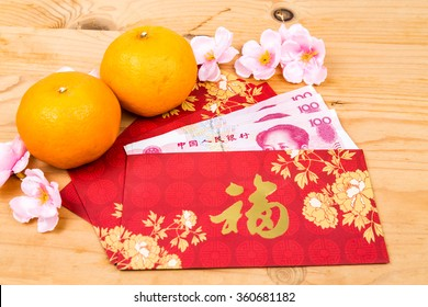Hung Bao or red packet with Good Fortune Chinese character filled with China Renminbi Yuan, displayed with mandarin oranges