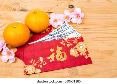 Hung Bao or red packet with Good Fortune Chinese character filled with US Dollar notes, displayed with mandarin oranges