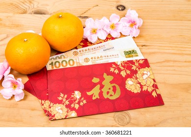 Hung Bao or red packet with Good Fortune Chinese character filled with Hong Kong Dollars, displayed with mandarin oranges