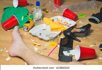 Hung over man passed out on the floor next day to a party, foot visible. Trash, food leftovers, clothes, high heels and bottles everywhere in messy house. Hangover, regret and remorse concept.