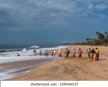 Hungama, Shri Lanka - February 09, 2019: fishermen at the beautiful lonely beach of Hungama, Shri Lanka, are pulling their net out of the water.
