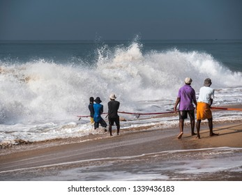 Hungama, Shri Lanka - February 09, 2019: fishermen at Hungama, Shri Lanka, are pulling their net out of the dramatic waves of the ocean