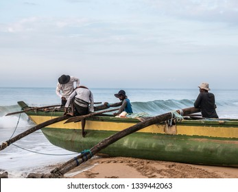 Hungama, Shri Lanka - February 09, 2019: fishermen at Hungama, Shri lanka, climb on their traditional outrigger boat. They are getting ready for fishing.