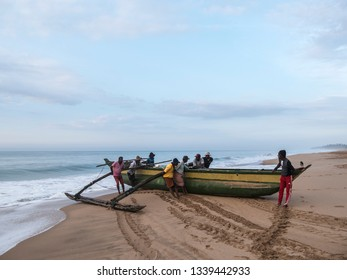 Hungama, Shri Lanka - February 09, 2019: fishermen at Hungama, Shri lanka, push their traditional outrigger boat into the water