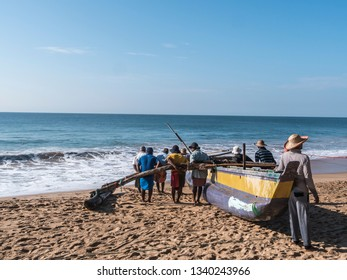 Hungama, Shri Lanka - February 10, 2019: fishermen at Hungama, Shri lanka, push their traditional outrigger boat up the beach after fishing