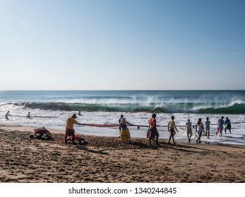 Hungama, Shri Lanka - February 10, 2019: fishermen at the beautiful beach of Hungama, Shri Lanka, are fishing from the beach. Here they pull their net out of the water.g