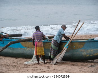 Hungama, Shri Lanka - February 11, 2019: fishermen at Hungama, Shri lanka, are working on their traditional outrigger boat.