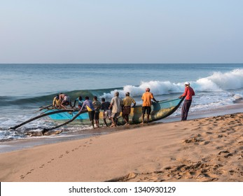 Hungama, Shri Lanka - February 11, 2019: fishermen at Hungama, Shri lanka, push their traditional outrigger boat through the surf into the ocean