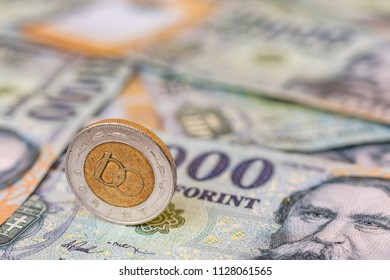 Hungarian 100 forint coin standing on its edge on 20000 forint banknotes