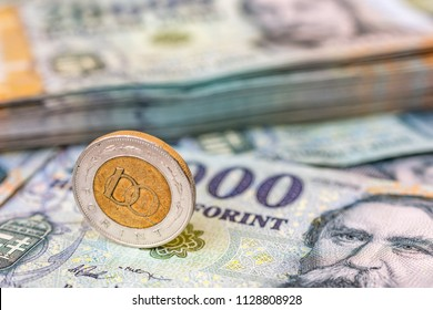 Hungarian 100 forint coin standing on its edge on 20000 forint banknotes with a stack of money in the background