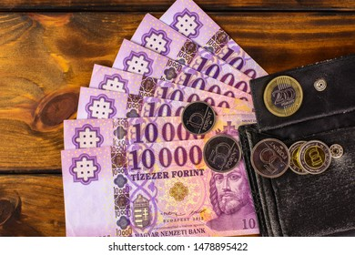 Hungarian banknotes and coins on a wooden table, 10 thousand forints and a wallet. Europe Hungary.