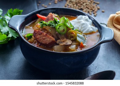Hungarian black garlic soup with lentils and kielbasa sausage