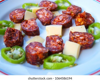 Hungarian breakfast compilation. Homemade smoked sausage slices, cheese pieces and green hot pepper slices on a white plate.