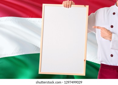 Hungarian Chef holding blank whiteboard menu on Hungary flag background. Cook wearing uniform pointing space for text.