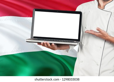 Hungarian Chef holding laptop with blank screen on Hungary flag background. Cook wearing uniform and pointing laptop for copy space.