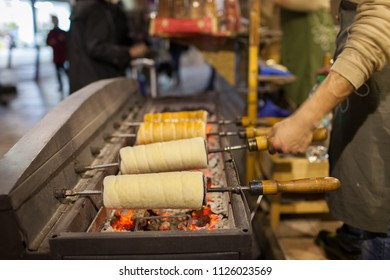 Hungarian chimney cakes being prepared on top of hot coals that are sold in the Christmas markets in Budapest, Hungary