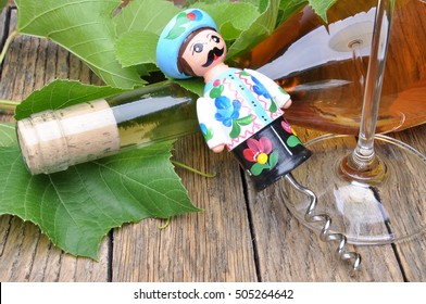 Hungarian decorative corkscrew, wine bottle and glass of wine on the wooden table with green twigs vine