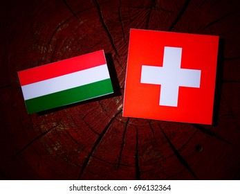Hungarian flag with Swiss flag on a tree stump isolated