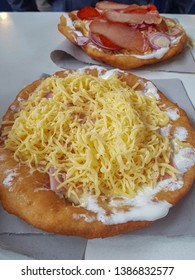 Lángos is a Hungarian food speciality, a deep fried dough topped with sour cream, cheese and any other toppings. Unhealthy fast street food. Traditional, a must try for locals and tourists a like.