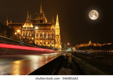 Hungarian Parliament building all lit up at night in Budapest, Hungary with car light streaks in the dark and full moon over the Danube River