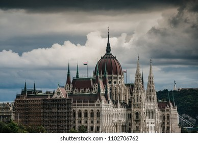 The hungarian parliament building with the Liberty statue on Gellert hill in the background dramatic clouds, Budapest, Hungary