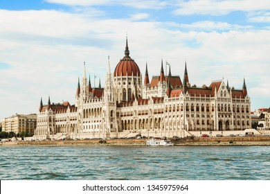 The Hungarian Parliament Building. The view from the opposite side of the Danube river. Cruise boat in the water.