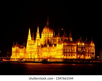 Hungarian Parliament in Neo Gothic style along the Danube in panoramic night view with tour boat under black sky. Famous and popular Budapest landmark and tourist attraction. Tourism & travel concept.
