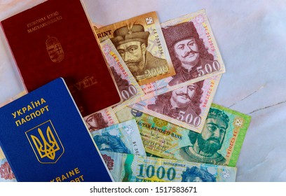The Hungarian passports and Ukrainian passport with money banknotes forints in dual citizenship