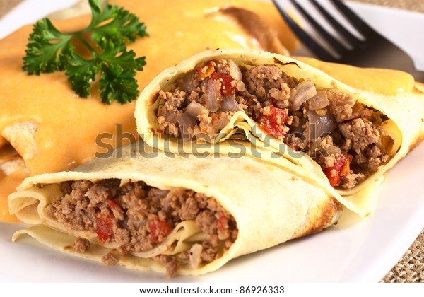 Hungarian-style crepe called Hortobagyi Husos Palacsinta (Crepe a la Hortobagy) filled with meat, tomato and onion amd served with sauce (Selective Focus, Focus on the stuffing in the upper half)