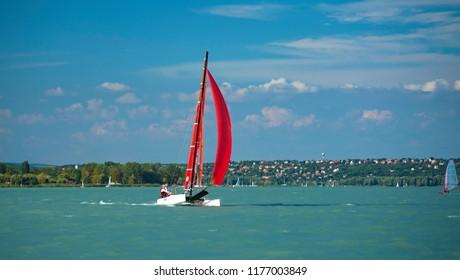 BALATONALMÁDI, HUNGARY - 17 AUGUST, 2018: Red catamaran on lake Balaton on 17 August, 2018.