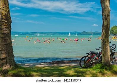 BALATONFÖLDVÁR, HUNGARY - 29 JULY, 2018: Tourists and sailboats on lake Balaton, Hungary on 29 July, 2018