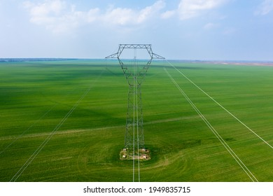 Lajoskomárom, Hungary - Aerial close-up view of electricity pylon with power lines over agricultural field.