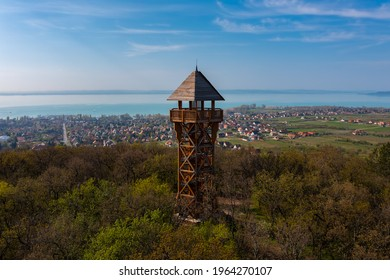 Alsóörs, Hungary - Aerial view about lookout tower on the top of Somlyo mountain, with lake Balaton at the background. Spring landscape.