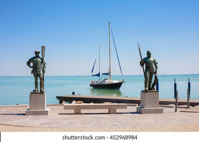 BALATONFU?RED, HUNGARY - AUGUST 03, 2013:  Fisherman and Rowing Man statues at the beach of Balatonfured with a sailboat in the backround on Lake Balaton, Hungary