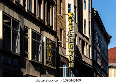 Hungary, Budapest: Big old yellow Stylbutor neon sign on a run down house facade in the city center of the Hungarian capital with blue sky - concept advertisment business evanescence. Feb 06, 2019