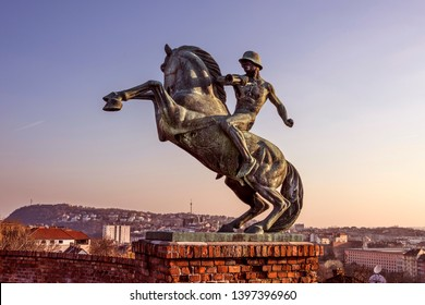 Hungary, Budapest: Equestrian statue of Mounted Messenger horseman at famous Royal Castle Hill near Fisherman's Bastion isolated with skyline of Hungarian capital in the backgroundl. Feb 06, 2019