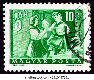 """HUNGARY - CIRCA 1964: A stamp printed in Hungary from the """"Transport and Communications"""" issue shows Girl pioneer and woman letter carrier, circa 1964."""